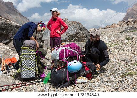 Group of People Man and Women Sitting Staying Along with Large Bags with Climbing Gear Attached such as Helmet Camping Mat Walking Poles Ice Axe