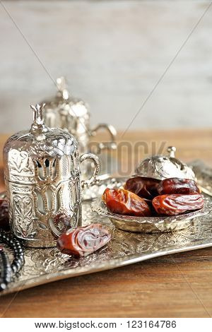 Composition of dried dates in holiday dish and rosary on wooden table