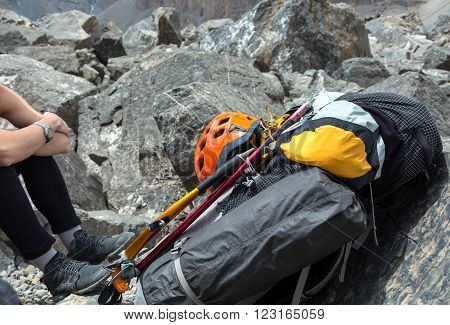 Backpack with Climbing Gear Attached Outside Sport Orange Protection Helmet Ice Axe and Hummer Mat and Tent Legs of Woman Left Side Rocky Terrain Background
