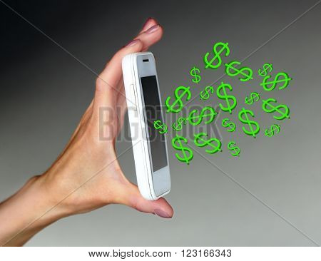 Making money online concept. Hand holding mobile smart phone with dollar bills coming out on gray background
