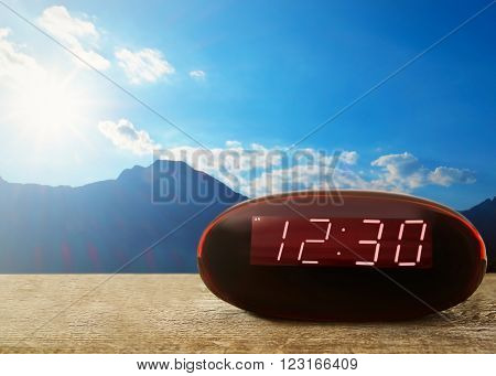 Digital clock showing 12:30 o'clock on wooden table, mountains on blue sky background