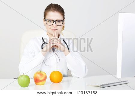 young beautiful female dietitian suggesting healthy fruit.