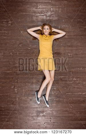 Top view creative photo of beautiful young woman on vintage brown wooden floor