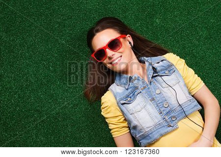 Beautiful young woman with headphones enjoys in music while lying down on grass.