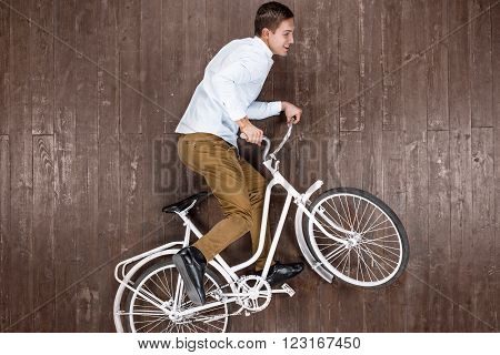 Top view creative photo of handsome young man on vintage brown wooden floor. Man riding on bike