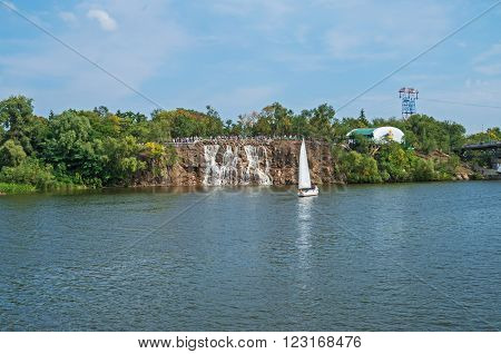 View of the green river island with waterfall on a clear sunny day