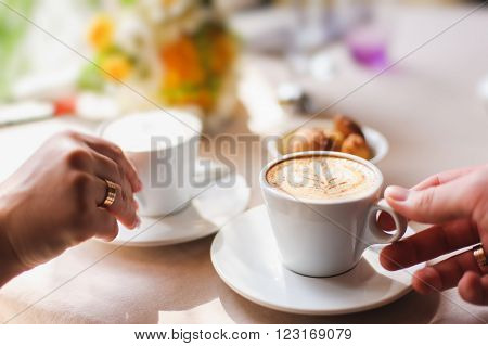 close-up, male and female hand holding a cup of coffee. couple in a cafe. focus on the crema, foam. light from a window. white cup of coffee on a saucer.