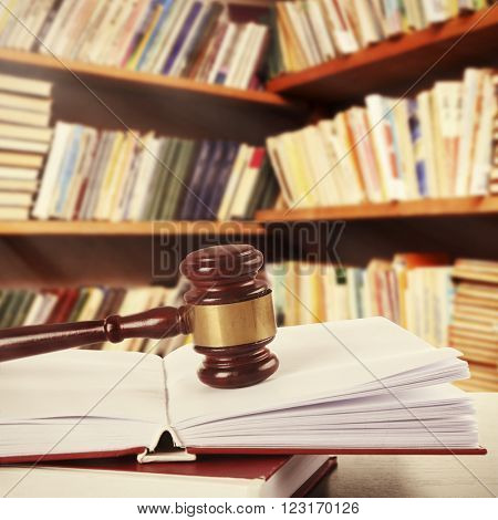 Wooden judges gavel lying on law book on table in library