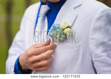 The man, the groom wears boutonniere. A man in a blue shirt, a white suit and a white tie. Hand corrects boutonniere.