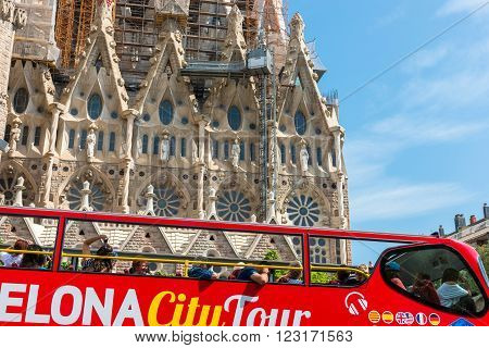 SPAIN BARCELONA - SEPTEMBER 13: People sitting on a double decker tourist coach in front of The Sagrada Familia Cathedral in Barcelona on September 13 2015