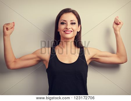 Pleased Strong Fit Woman Showing Muscle Biceps With Happy Smiling. Toned Vintage Portrait