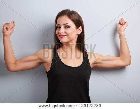 Pleased Strong Young Woman Showing Muscle Biceps With Smiling On Blue Background