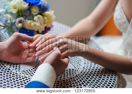 Man's and woman's hands on the table in cafe. Bride and groom holding hands. lace tablecloth, a bouquet in the background, focus on hand. Ring on the hand.