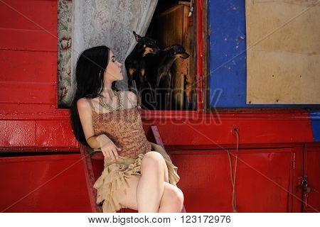 Fashionable girl guarded by two toy terrier dogs. Behind the scenes of the circus. On background of red-blue circus trailer