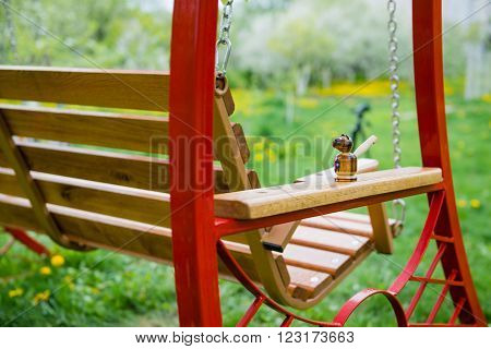 Swing bench near children house in garden with trees and grass