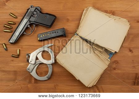 Gun and book crime and punishment. Place for your text. Gun and a book on wooden background.