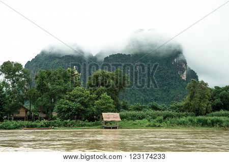 Lonely pavillion in riverside with tropical mountain in background