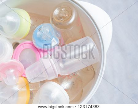 Nipple teethers and milk bottles in steam sterilizer and dryer. Steam sterilizer used for sterilize baby accessories by high temperature steam.