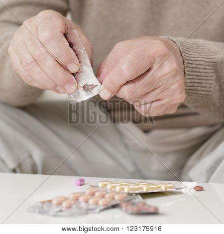 View at senior man taking his pills