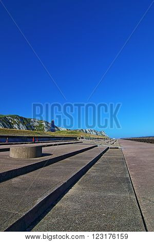 Samphire Hoe Tower at Cliffs of Dover Seawall on a sunny day