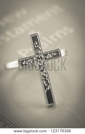 Crucifix ring on bible with seipa background.