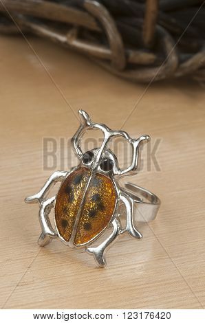 A silver  ladybird or ladybug ring on a laminated wooden table with a wooden basket in the background,