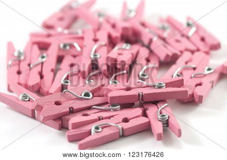 A pile of pink wooden clothes peg / pins on a white background.