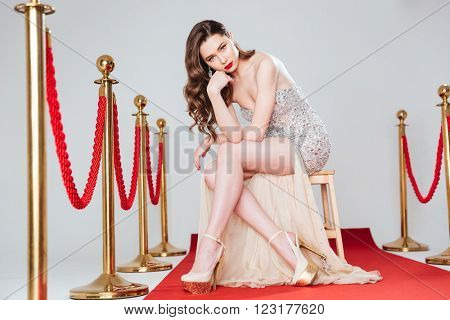 Charming woman sitting on the chair and looking at camera on red carpet