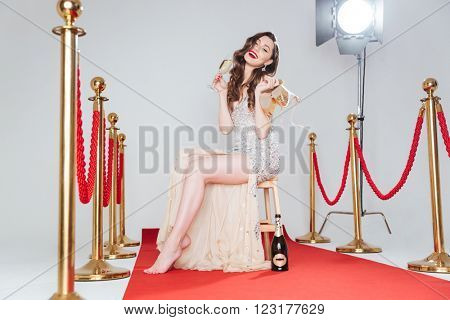 Smiling woman holding her heels and drinking champagne on red carpet