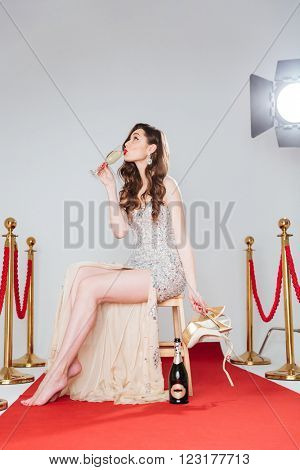Charming woman sitting on the chair and drinking champagne on red carpet