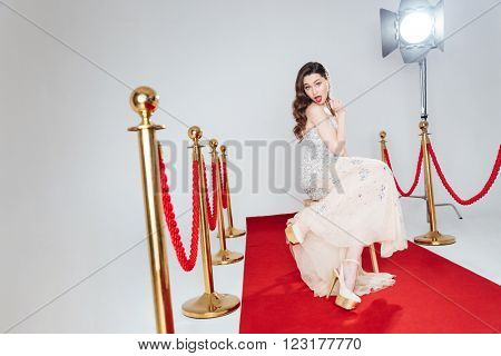 Charming woman sitting on the chair on red carpet and looking at camera