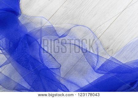Folded blue chiffon on gray wooden floor as a background