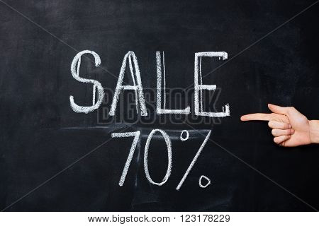 Hand pointing on seventy percent sale drawn on blackboard with chalk