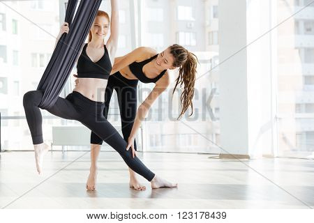 Happy pretty young woman doing aerial yoga with trainer in studio