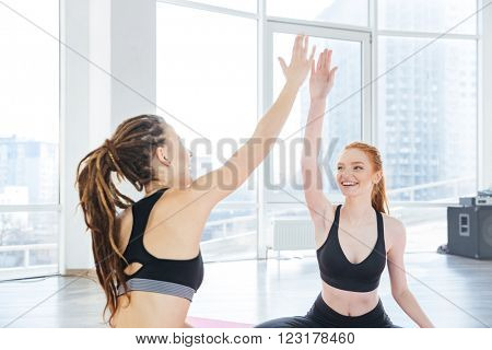 Two happy attractive young sportswomen giving high five after training