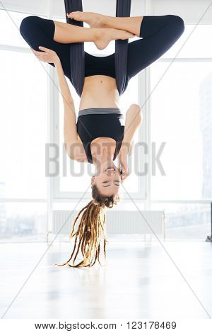Cheerful young woman doing aerial yoga and talking on mobile phone in stusio