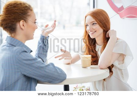 Two smiling attractive young women drinking coffee in cafe together