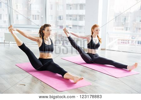 Two attractive young women stretching legs and practicing yoga in studio