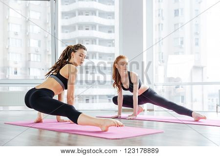 Two beautiful young women stretching legs together in yoga studio