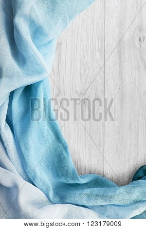 Blue draped cloth over white wooden background