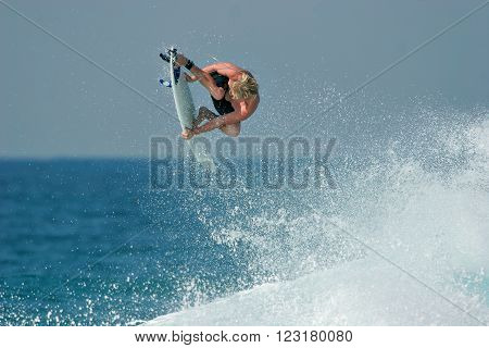 A surfer launches into the air above a beautiful blue wave, executing a radical aerial maneuver.