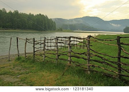 Lath Fence Near River Katun In Altai Mountains On The Sunset, Russia