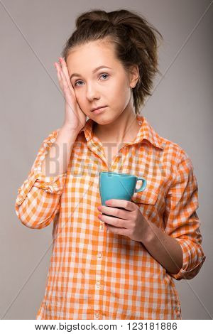 Studio Portrait Of A Sleepy Woman In An Orange Shirt With A Cup Of Coffee In Hand