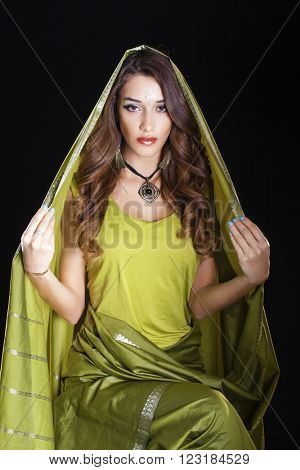 Young beautiful brunette woman in green indian dress, isolated on black background