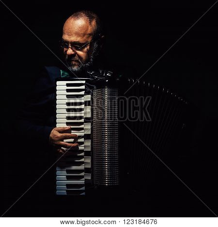 Portrait of an accordion player, playing and posing.