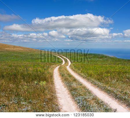 rut road across meadow under nice clouds in sky