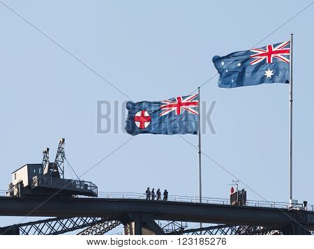 Sydney - February 25 2016: Flag of Australia and the Federal Capital Territory Flag develop over the famous Sydney Harbour Bridge and the tourists on the bridge Feb. 25 2016 Sydney Australia