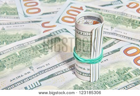 Many American One Hundred Dollar Bills packed in roll. Money cash background
