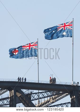 Sydney - February 25 2016: Flag of Australia and the Federal Capital Territory Flag develop over the famous Sydney Harbour Bridge and tourists standing on the bridge Feb. 25 2016 Sydney Australia