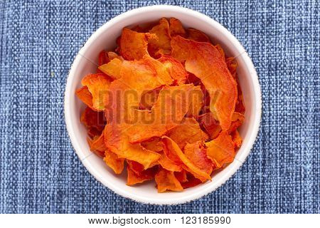 High angle directly above bowl full of thin sliced dehydrated papaya on blue fabric placemat